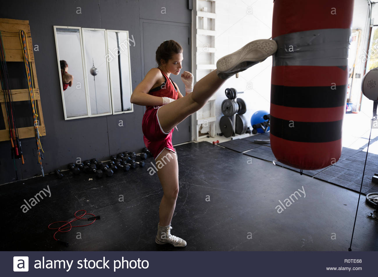 Hembra kickboxer pateando saco de boxeo en el gimnasio Imagen De Stock
