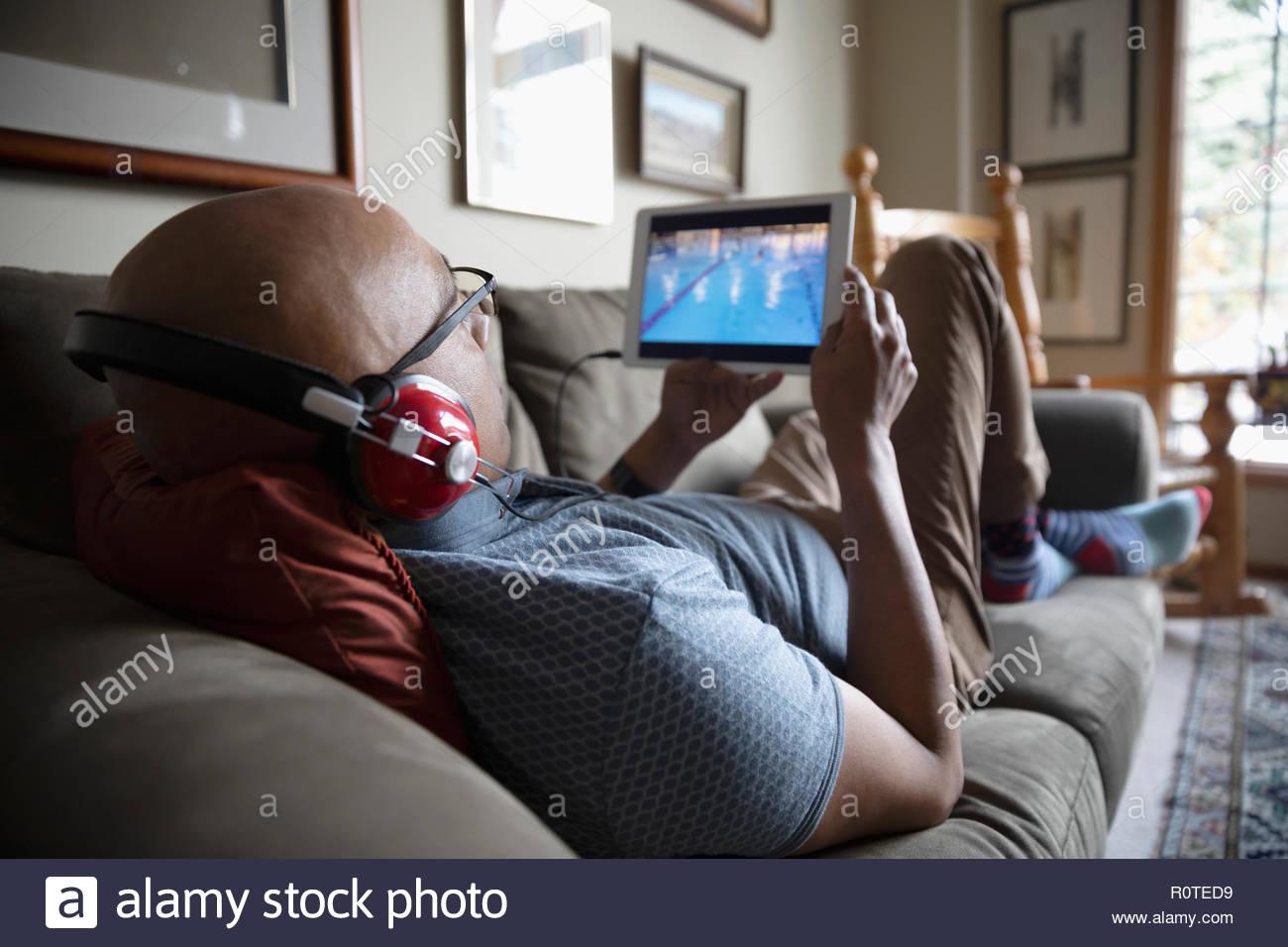 Hombre Latinx con auriculares viendo los deportes con la tableta digital en el sofá Imagen De Stock