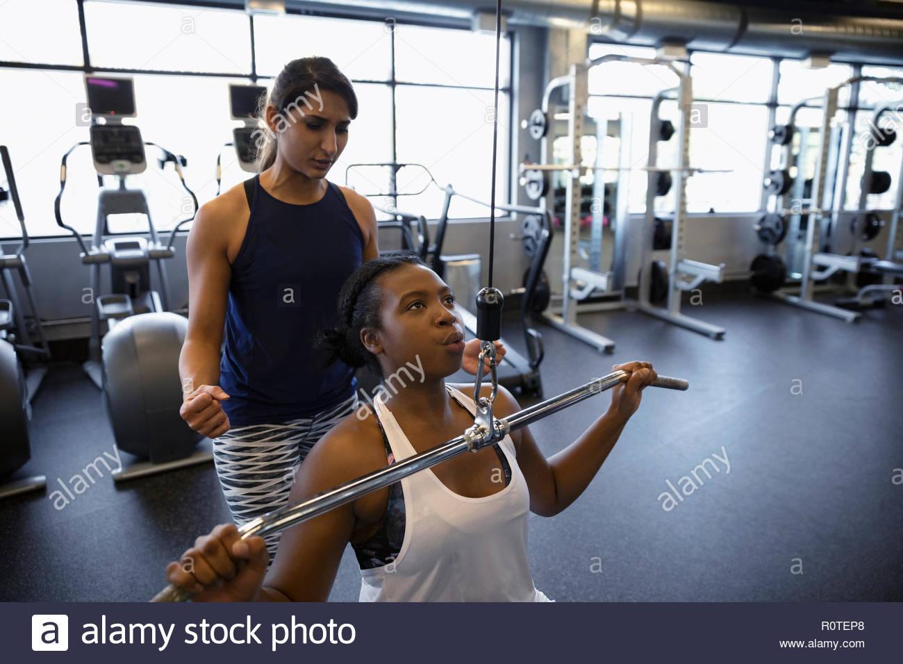 Entrenador personal ayudando a la mujer utilizando equipo de ejercicio en el gimnasio Imagen De Stock