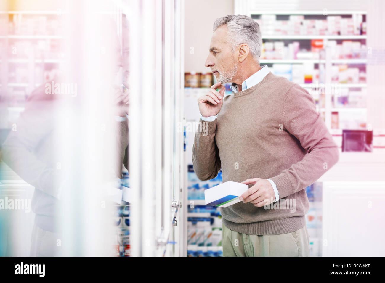 El hombre canoso mirando cuidadosamente en caso de vidrio Foto de stock