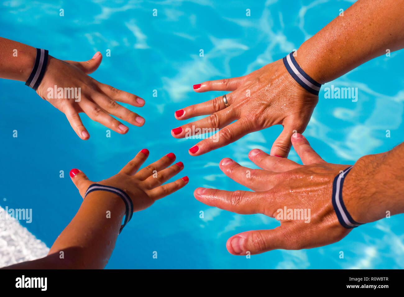 b173a3bc53c8 Las manos de la familia con todo incluido pulseras por recurrir a la  piscina. Los