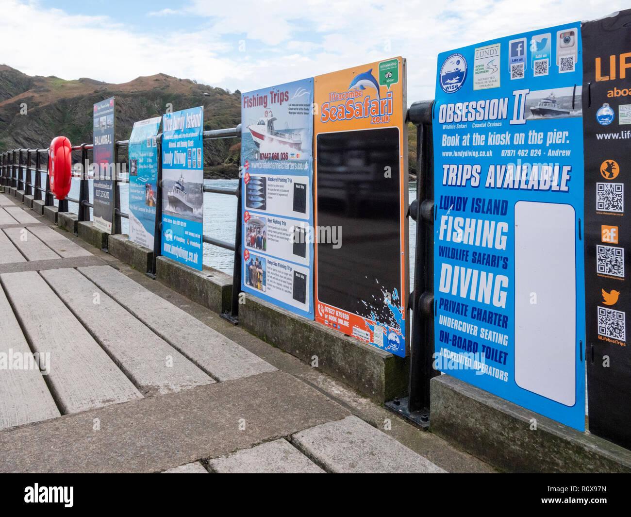 Los viajes de turismo y viaje en barco carteles publicitarios en Ilfracombe Harbour Devon UK en húmedo fuera de temporada o día de otoño Imagen De Stock