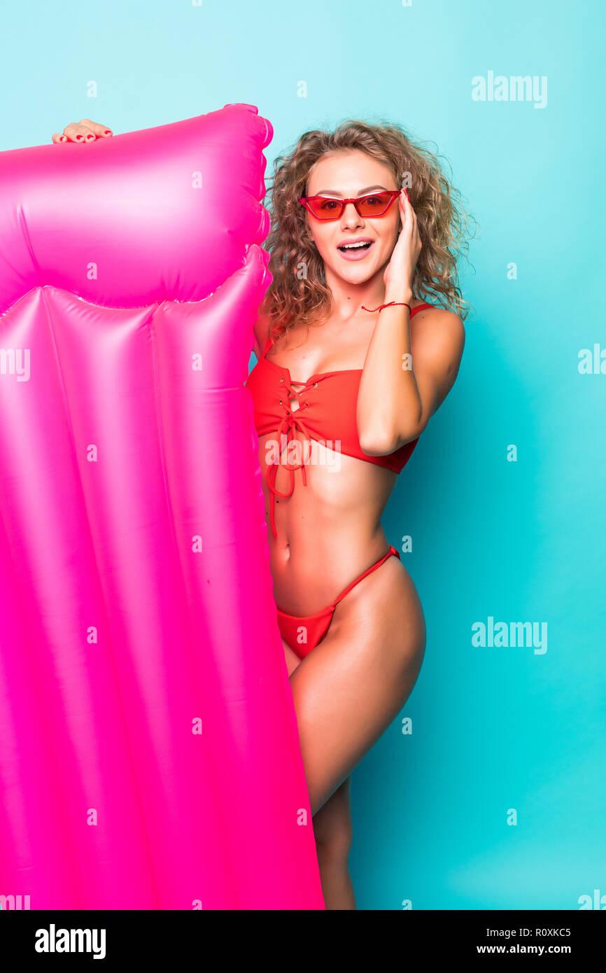 1eb7ef56ad7b Hermosa mujer vestida de rojo bañador y gafas de sol posando con rosa  colchón inflable aislado