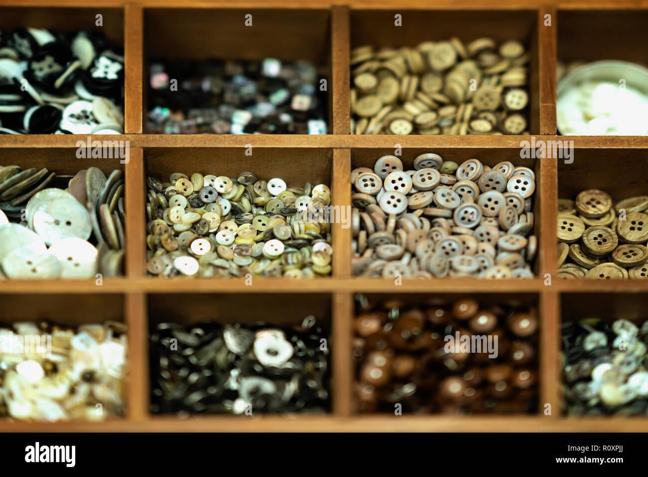 Distintos botones multicolores en cajas de madera para la creatividad, una verdadera tienda, selectiva de fondo. La industria textil, la confección, aficiones, handmade Foto de stock