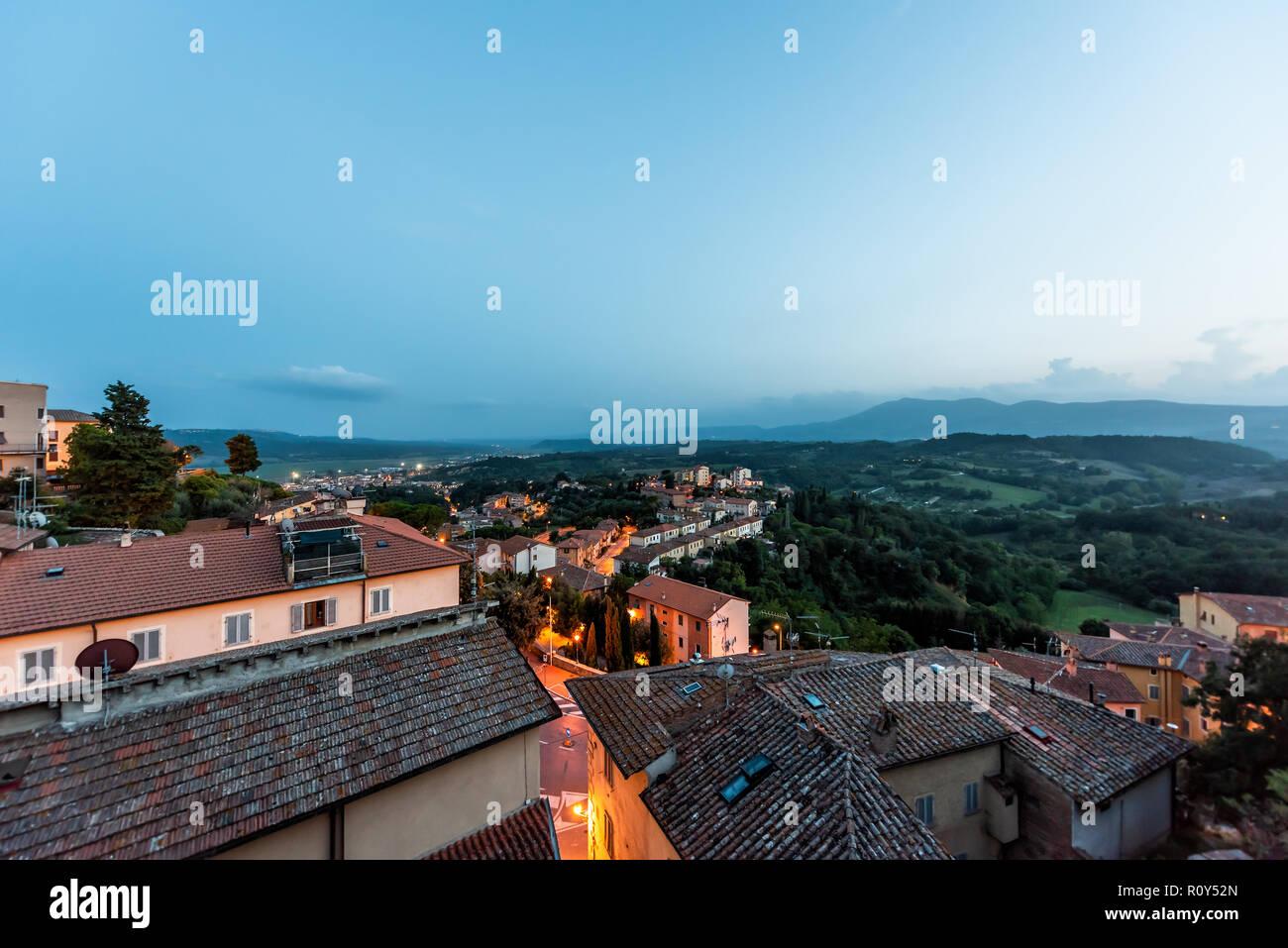 En Chiusi niebla niebla de noche, tarde o mañana en Umbría, Italia, cerca de Toscana, iluminado con luces en las calles, casas de la azotea en la montaña campo, r Foto de stock