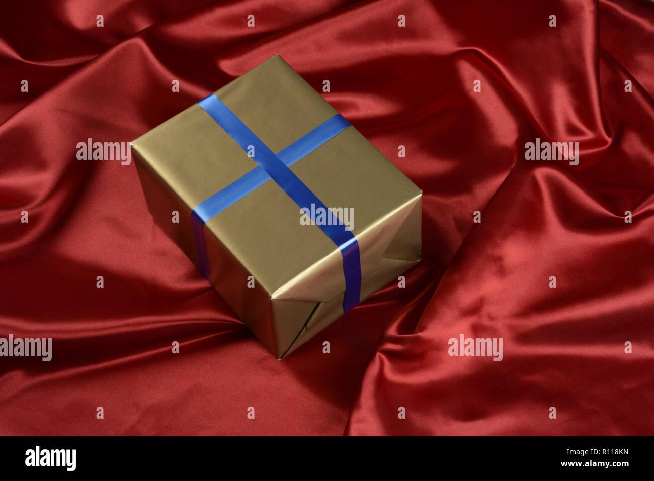 Caja de regalo de color dorado sobre fondo de tela de color rojo Imagen De Stock