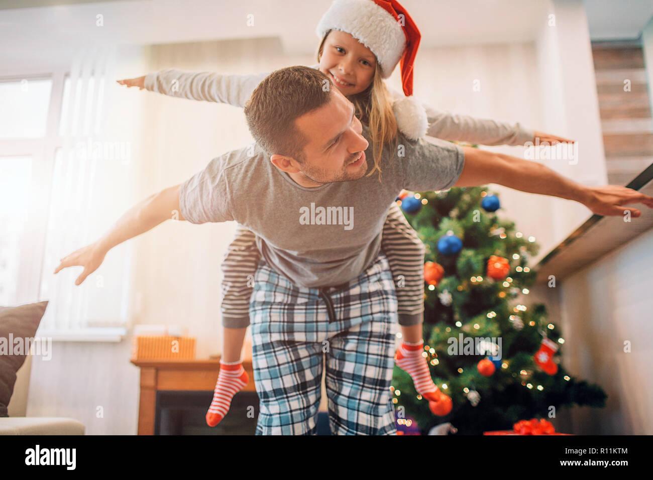 Padre e hija jugando en la habitación. Él monta sobre su espalda. Que mantiene las manos a un lado del cuerpo. Joven mira a la niña. Sonríen. La gente positiv Imagen De Stock