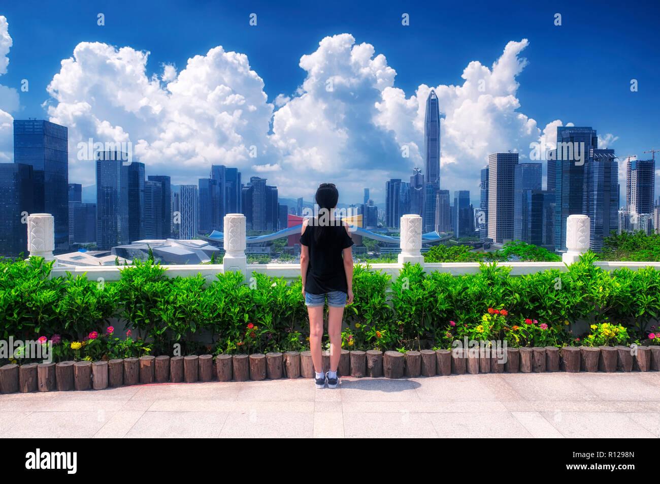 Una mujer china mirando a la ciudad de Shenzhen, China en un día soleado cielo azul. Imagen De Stock