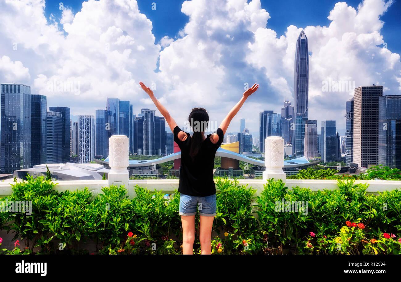 Una mujer china mirando a la ciudad de Shenzhen, China en un día soleado cielo azul de lianhuashan park. Imagen De Stock
