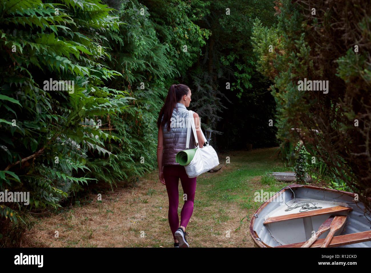 Mujer que llevaba paseando por el jardín de la estera del yoga Foto de stock