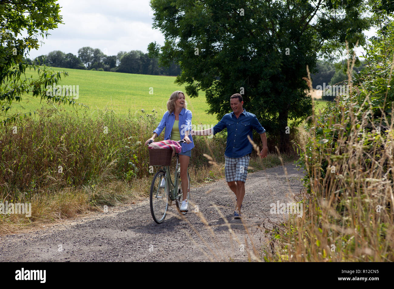 Pareja paseando y ciclismo en carretera rural Foto de stock