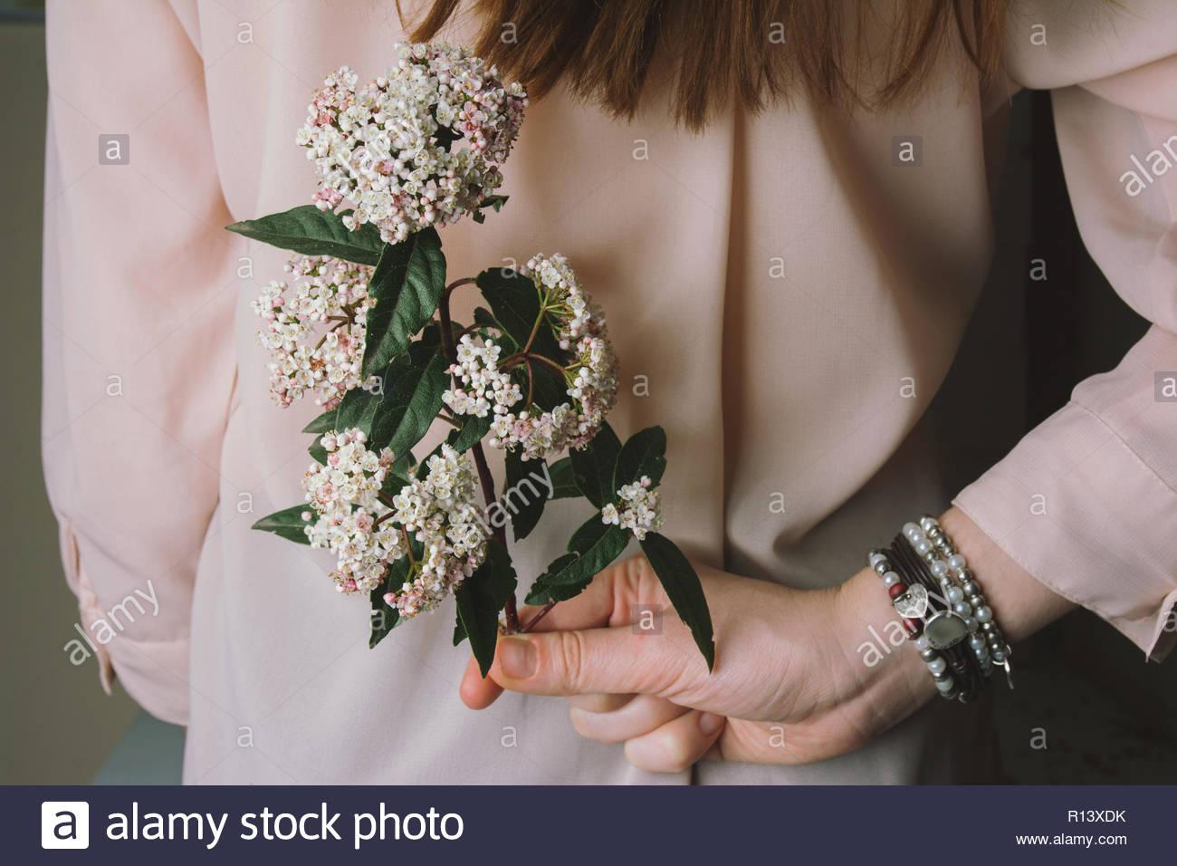 La mitad del torso de una mujer sosteniendo un ramo de flores a la espalda Imagen De Stock