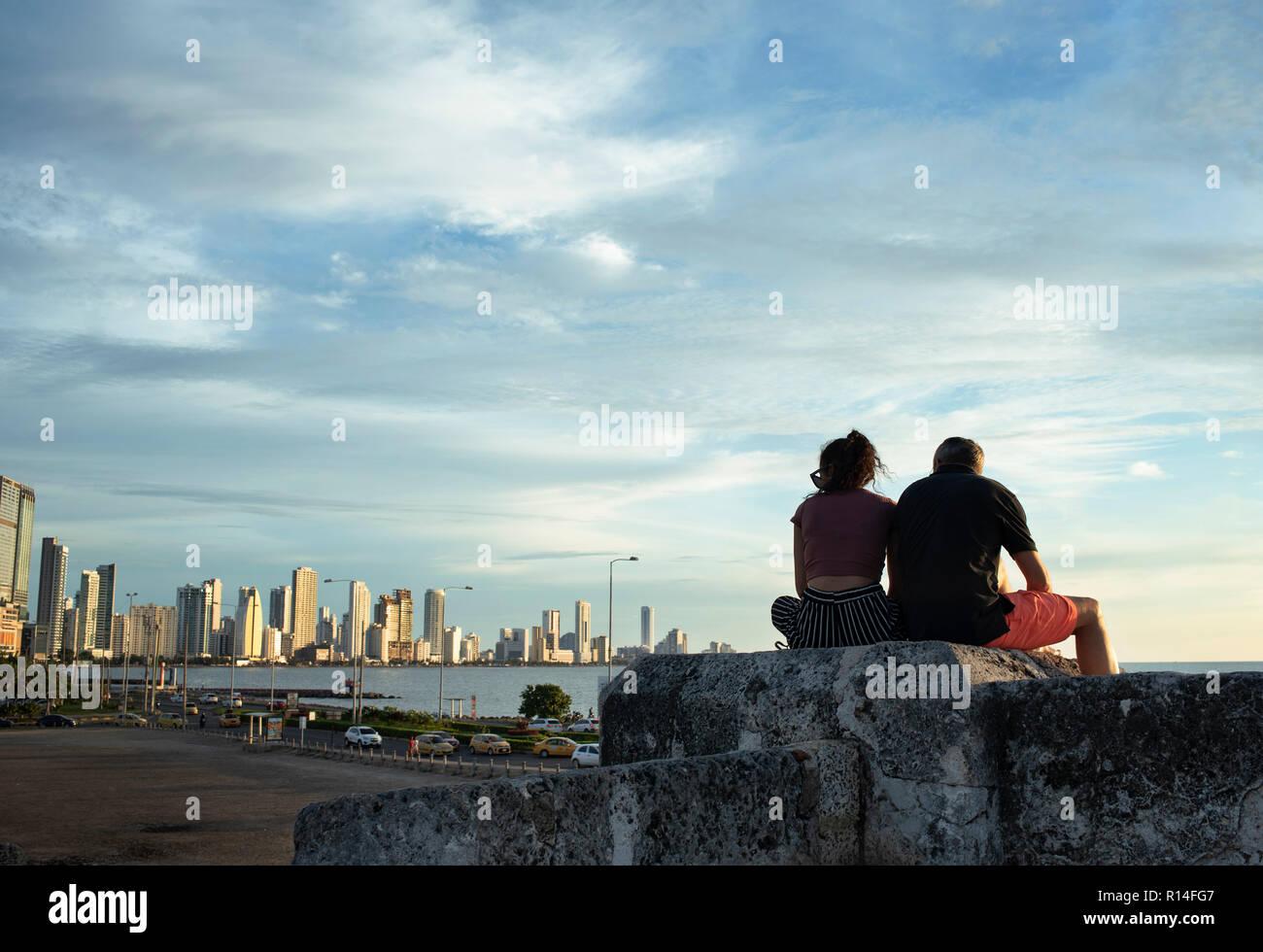 La pareja se asienta en la cima de la pared de piedra de la 'Ciudad Vieja' viendo el horizonte del nuevo barrio Bocagrande. Cartagena de Indias, Colombia. Oct 2018 Foto de stock