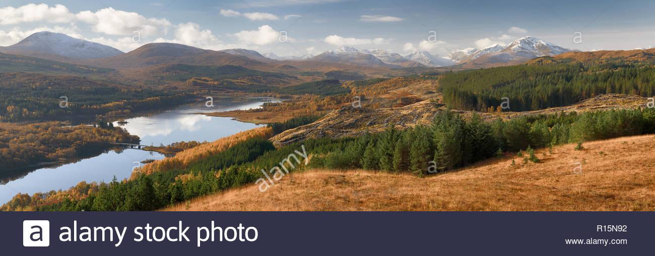 Una vista panorámica mirando al Loch Garry y las nevadas montañas Knoydart durante una soleada mañana de otoño Foto de stock