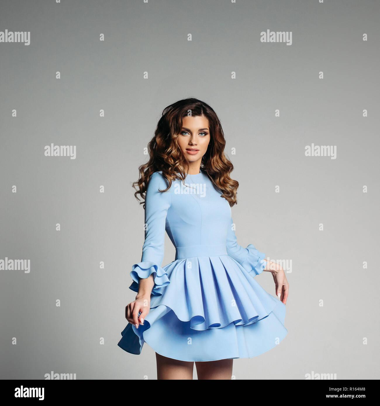 2a6c54107 Retrato de estudio de bella mujer con largo cabello ondulado y ojos azules  impresionantes vestidos de bonito vestido con volantes en azul claro sobre  fondo ...