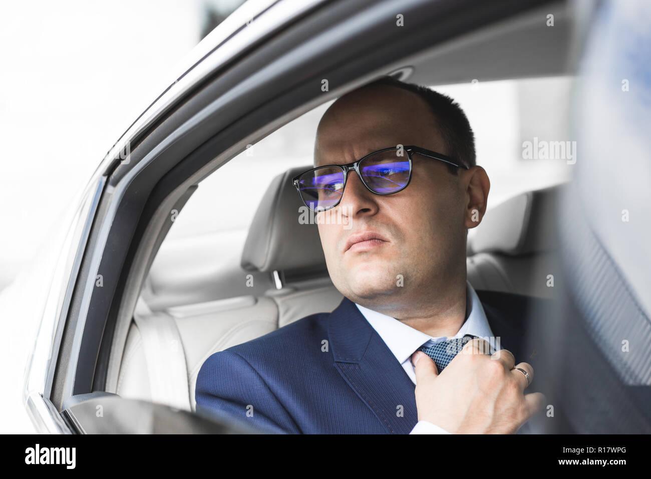 5ee543adff Joven Empresario de éxito habla por teléfono sentado en el asiento trasero  de un coche de