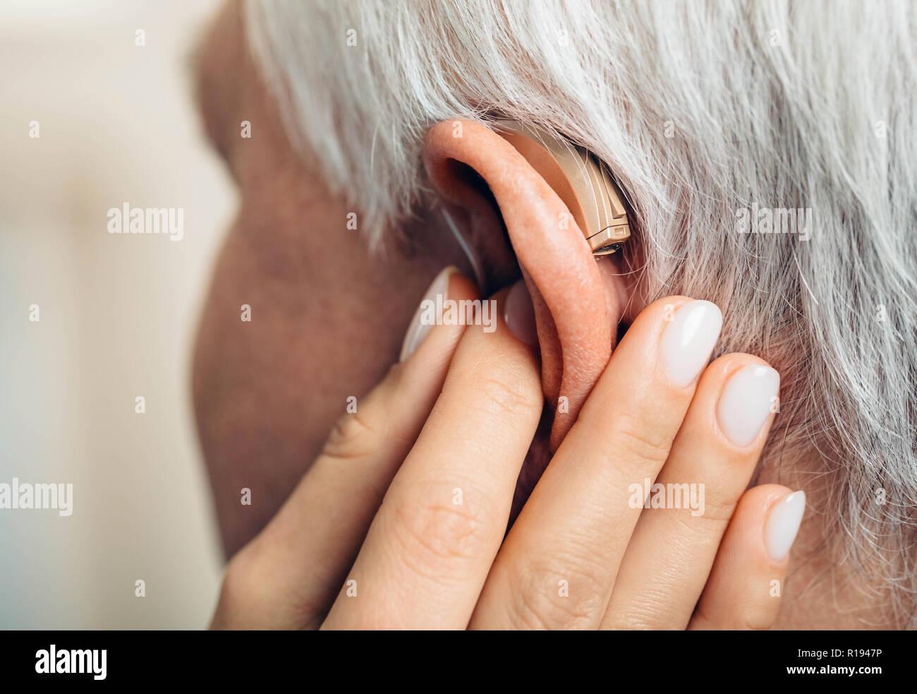 Ajuste de un audífono para un hombre envejecido Imagen De Stock