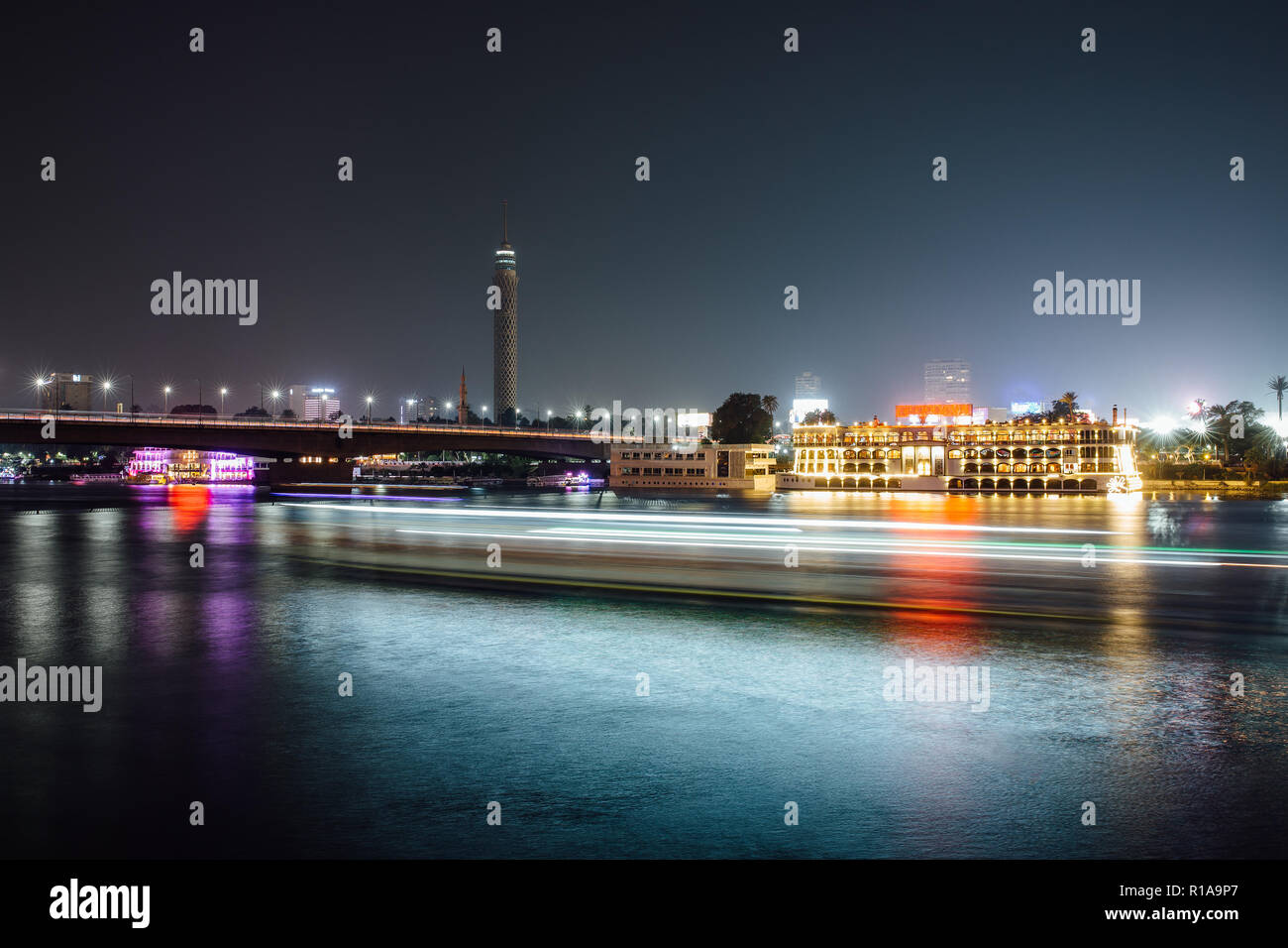 El centro de la ciudad de El Cairo por la noche, la larga exposición con estelas de luz moviéndose de botes en el río Nilo. Foto de stock