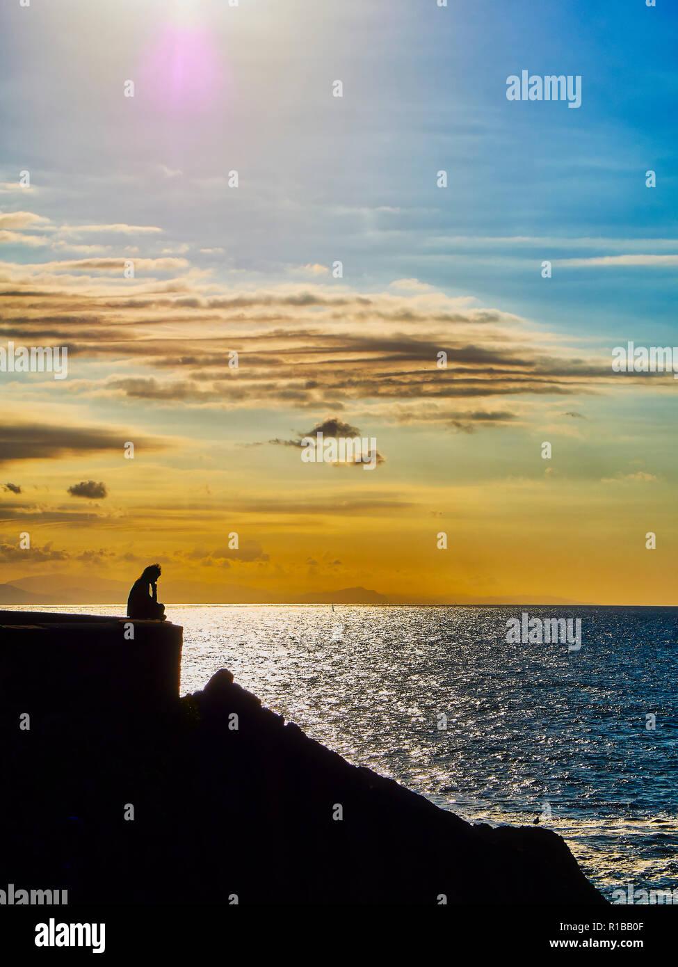 Pensativo silueta de una mujer sentada sobre una pared frente a un fondo en penumbra. Imagen De Stock