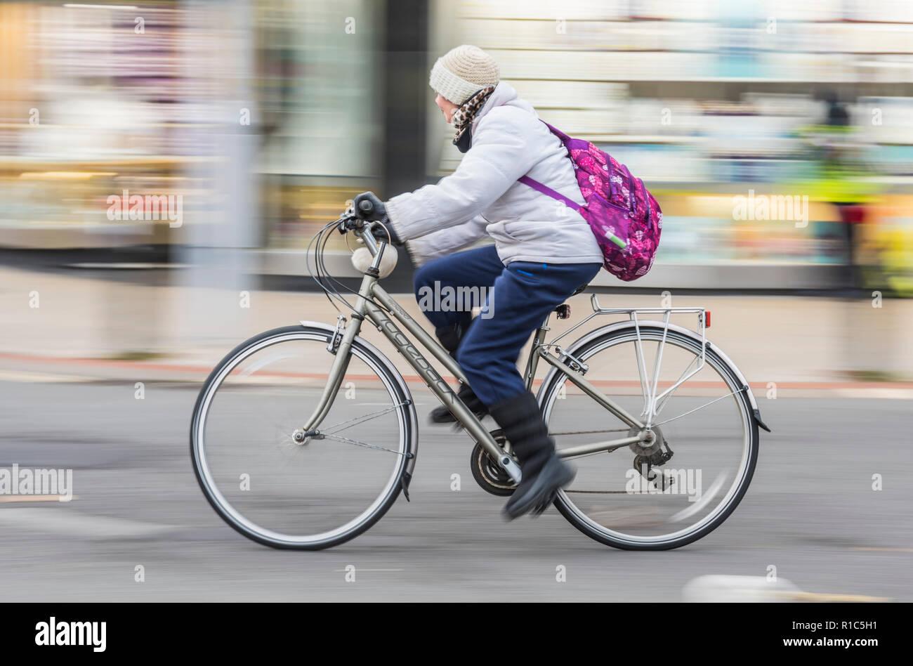 Vista lateral de la mujer de mediana edad montando una bicicleta de cresta dorsal vistiendo sombrero, abrigo y la mochila, mostrando el desenfoque de movimiento, Reino Unido. Ciclismo femenino. Ciclista femenino. Imagen De Stock