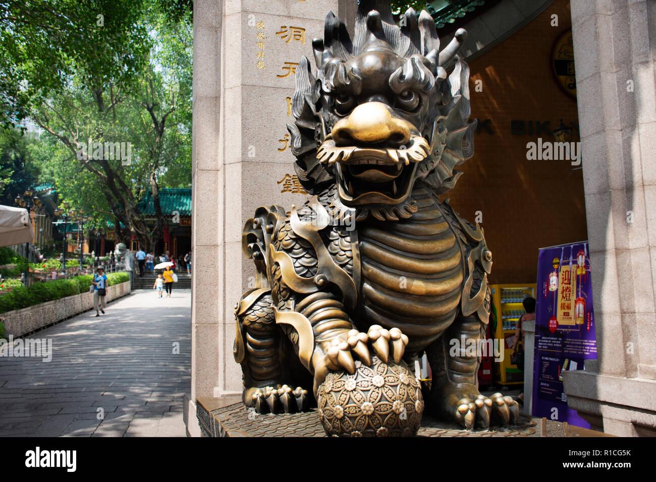 La escultura de piedra dragón Qilin guardián en la entrada del templo de Wong Tai Sin gente visita y respeto orando en Kowloon, el 9 de septiembre de 2018, en Hong Foto de stock