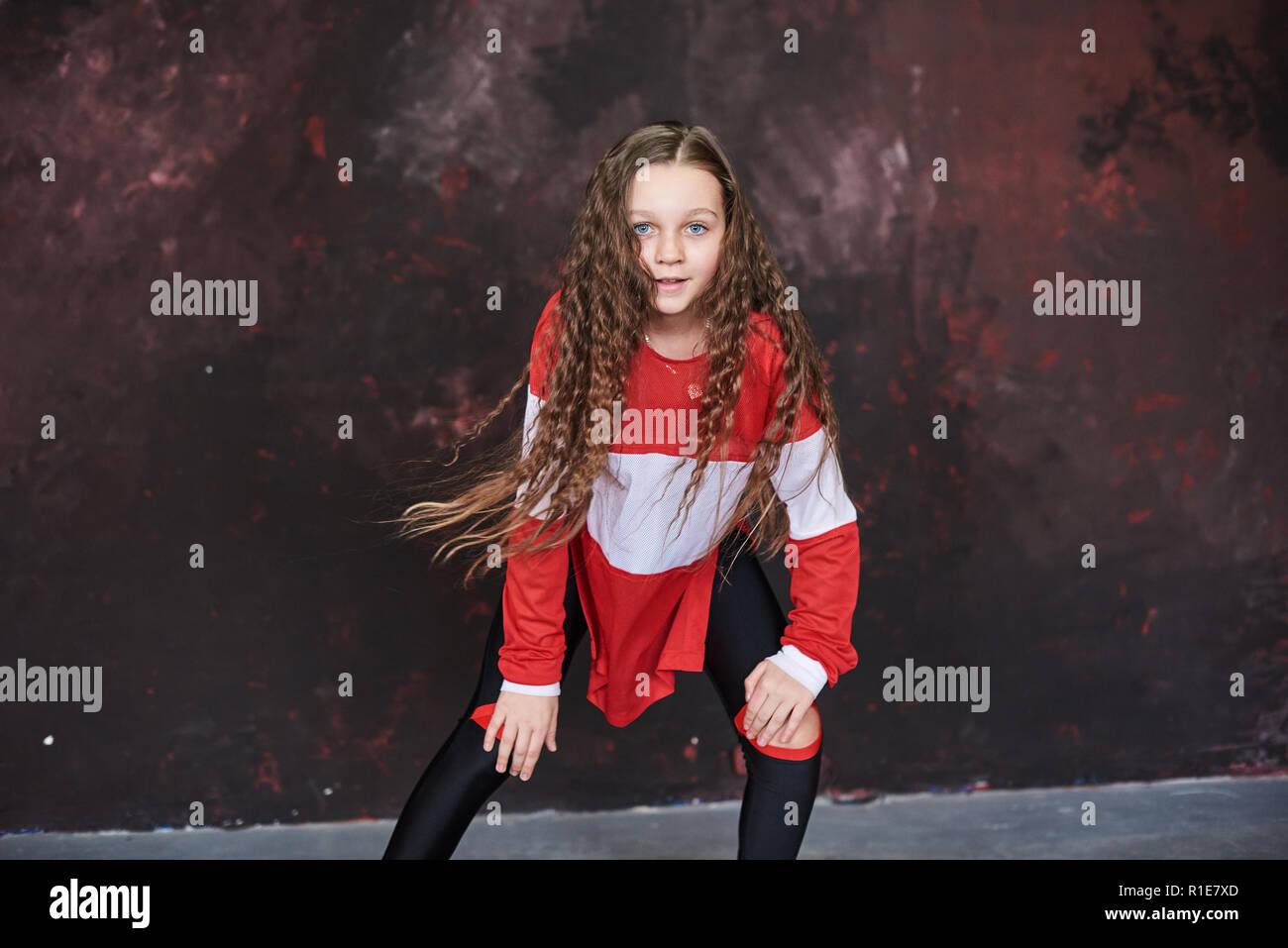 Hermosa joven bailando en ropa de moda en un fondo grunge Imagen De Stock 95e20ab0e64