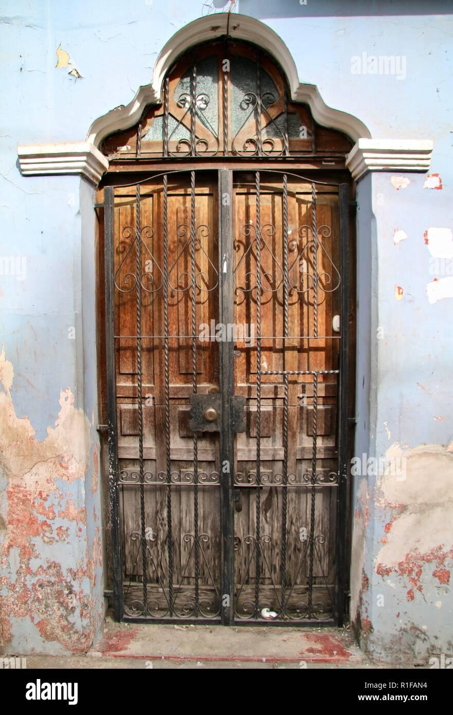 Puerta de madera desgastada centroamericanos en un cielo azul con rejilla metálica que cubre la pared Foto de stock