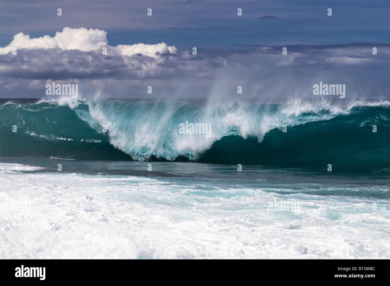 Ola enrollan en playa hawaiana, a punto de estrellarse en el agua por debajo. Volver a rociar flyng superior del wave. South Point. Mar Blanco spray lanzados al aire. Foto de stock