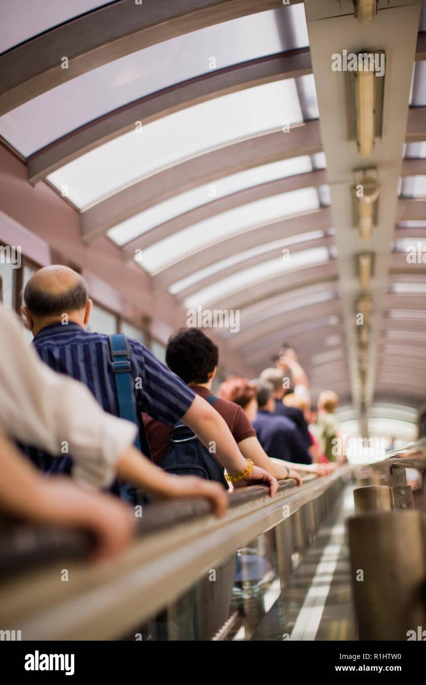 Grupo de personas que se desplazan hacia arriba en una escalera mecánica. Imagen De Stock