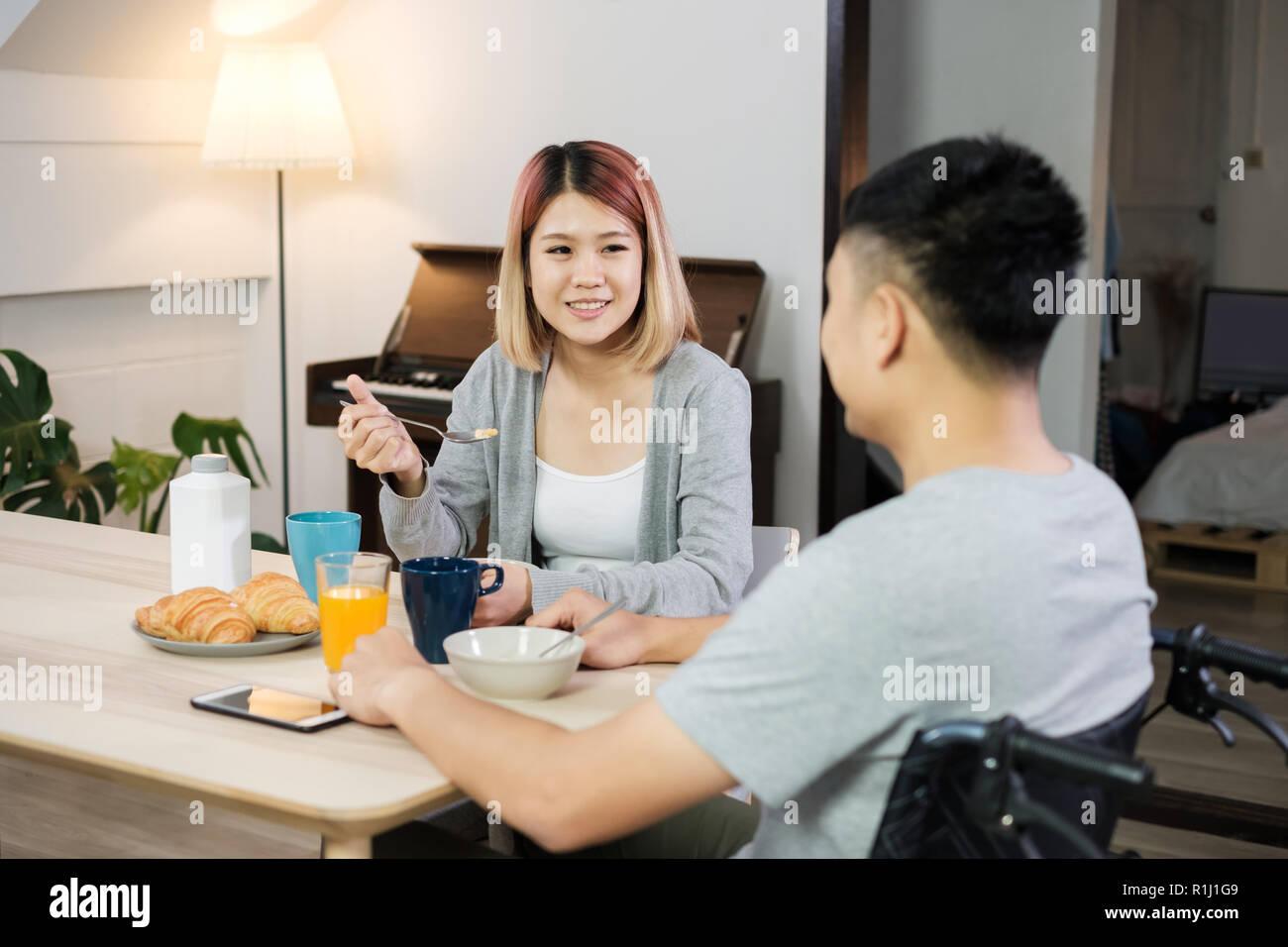 Par de Asia desayuno en casa.esposa sosteniendo la mano y alentar el marido inválido sentado en la silla de ruedas en la mesa de la cocina.pareja en inicio concepto Foto de stock