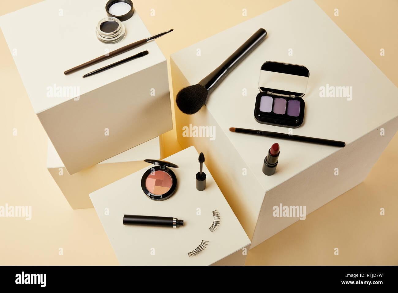 Un alto ángulo de visualización de diversos accesorios para maquillaje en cubos de color beige Foto de stock