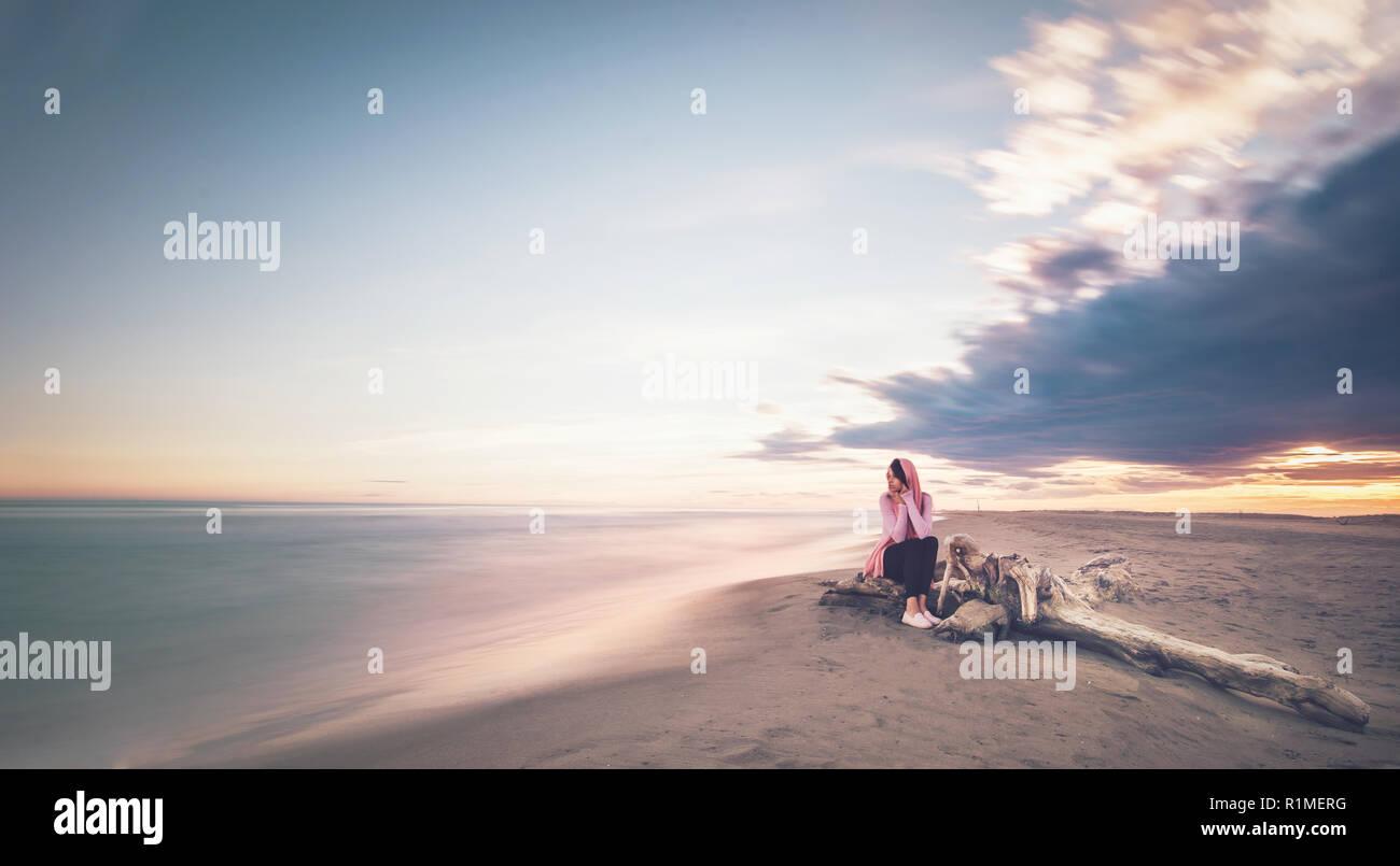 Mujer sentada por el mar en una playa paradisíaca isla, rodeada por el paraíso, bonito atardecer o amanecer Foto de stock