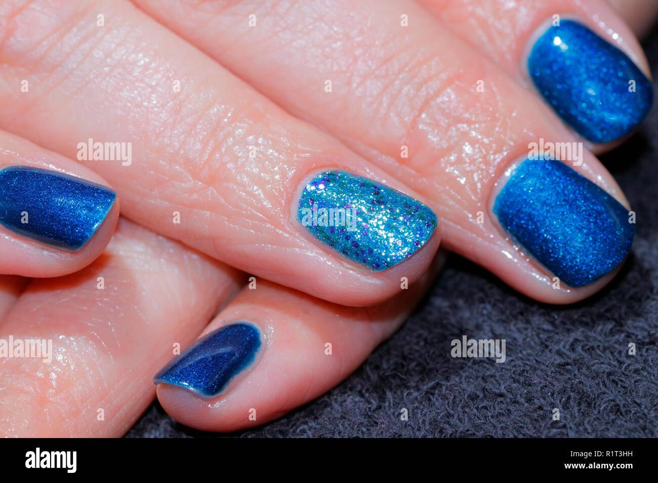Chispeante glitter azul uñas después sólo se aplica en un salón de uñas. Foto de stock