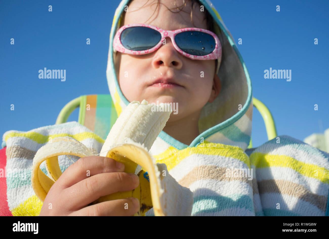 Niño de 3 años con una toalla con capucha Poncho. Él está comiendo banana  después 24680efdd80