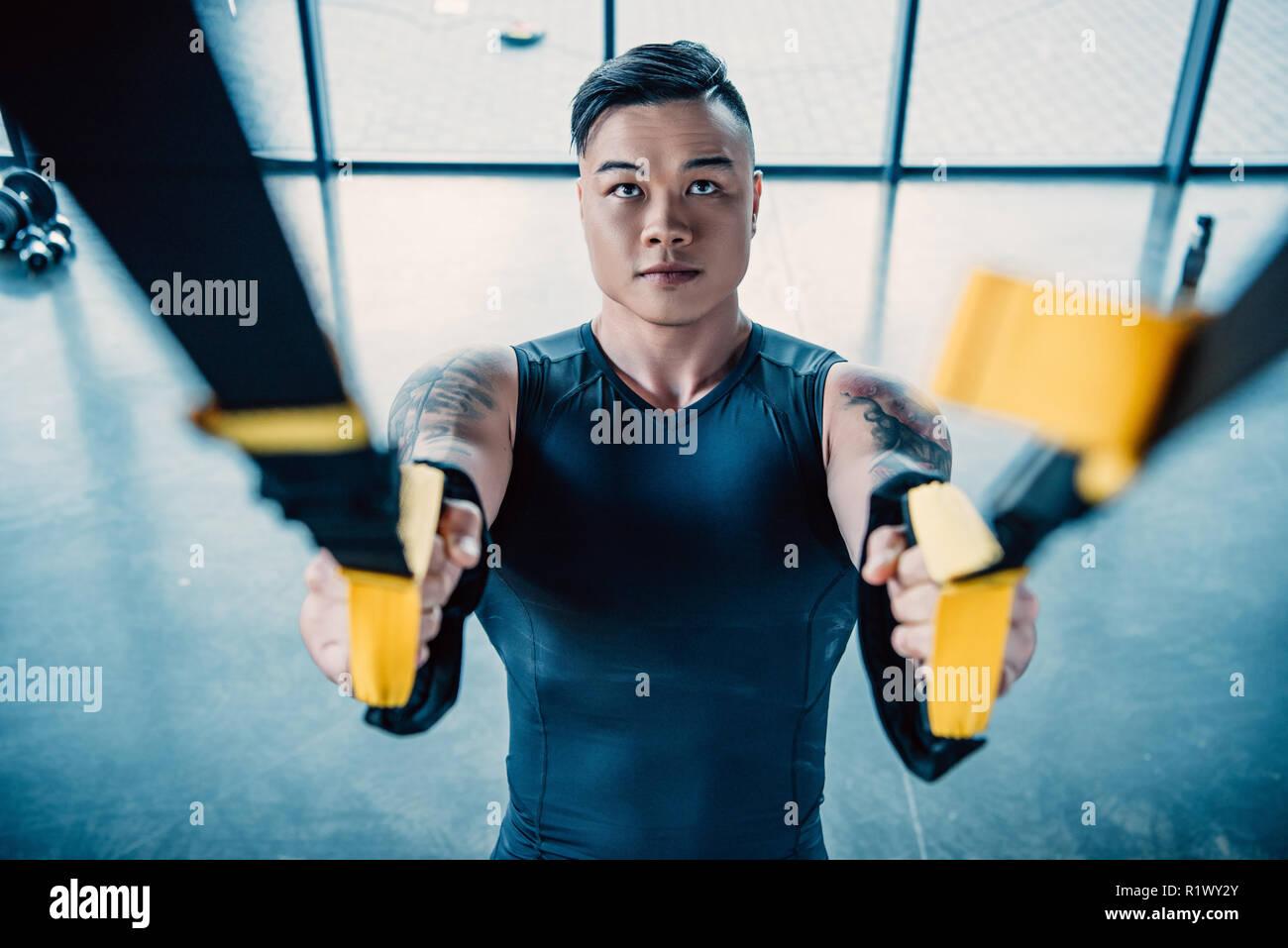 Centrado joven deportista entrenamiento muscular con bandas de resistencia en el gimnasio Foto de stock