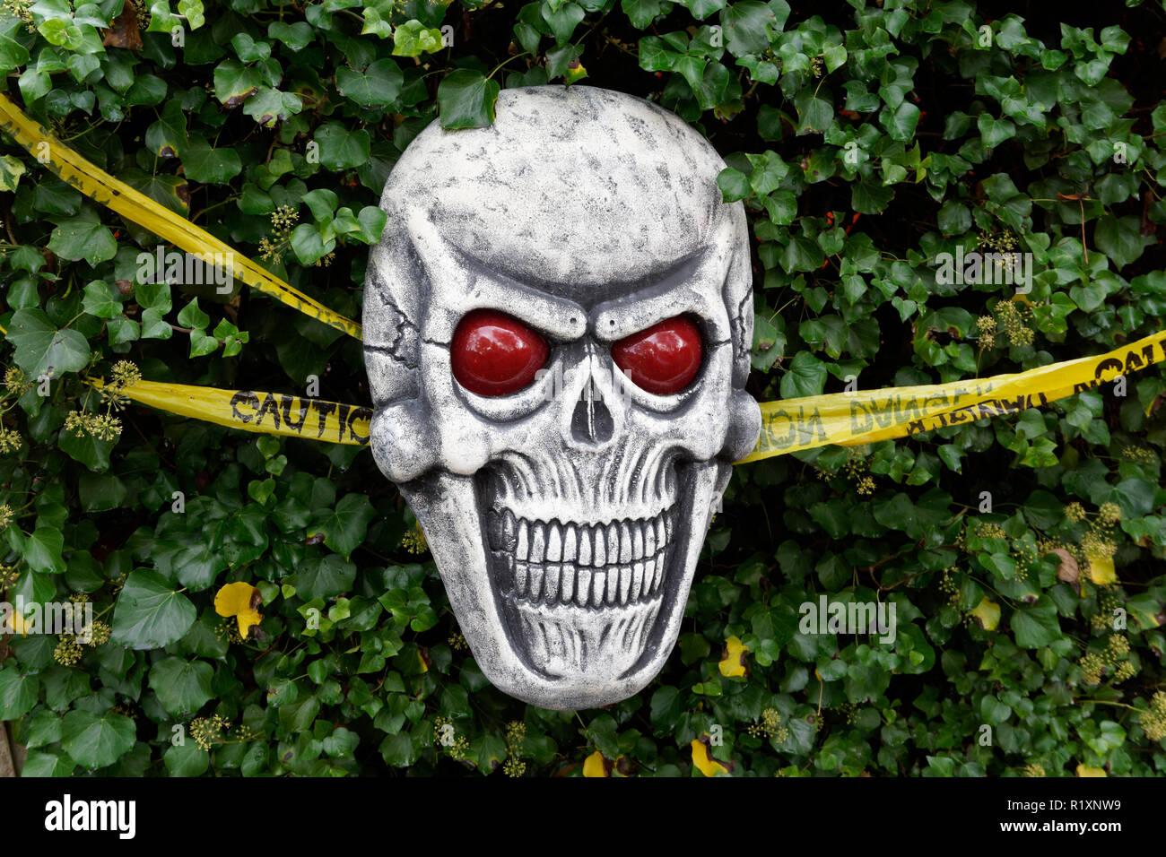 Espantosa calavera sonriente decoración de Halloween en un jardín. Imagen De Stock