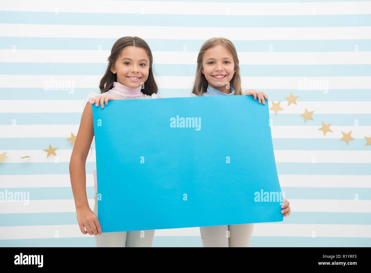 Concepto de anuncio para niños. Increíble noticia sorprendente. Chica mantenga anuncio banner. Las niñas niños sosteniendo pancartas de papel para el anuncio. Los niños felices con el papel en blanco el espacio de copia de anuncio. Imagen De Stock