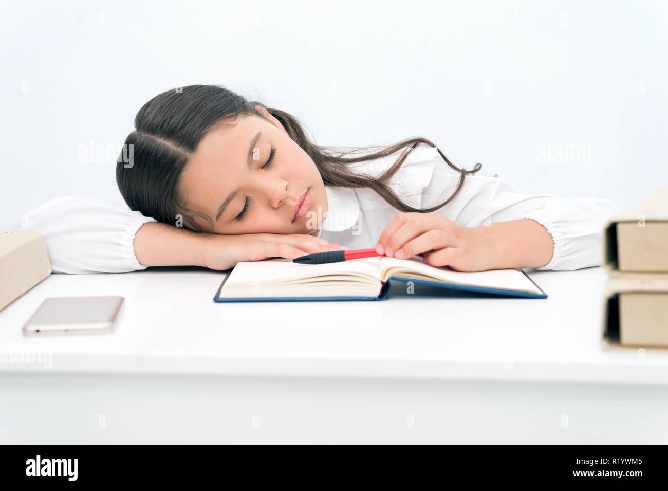 Concepto de NAP. Cansado schoolgirl tienen pan. Niña tomando pan en la mesa. Es la hora de la siesta. Imagen De Stock