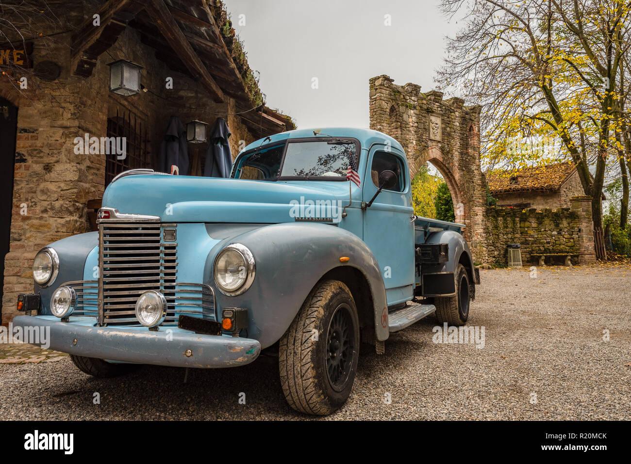Histórico del recogedor de color azul, estacionado en las calles de un histórico pueblo italiano, coches clásicos americanos, imagen horizontal Foto de stock