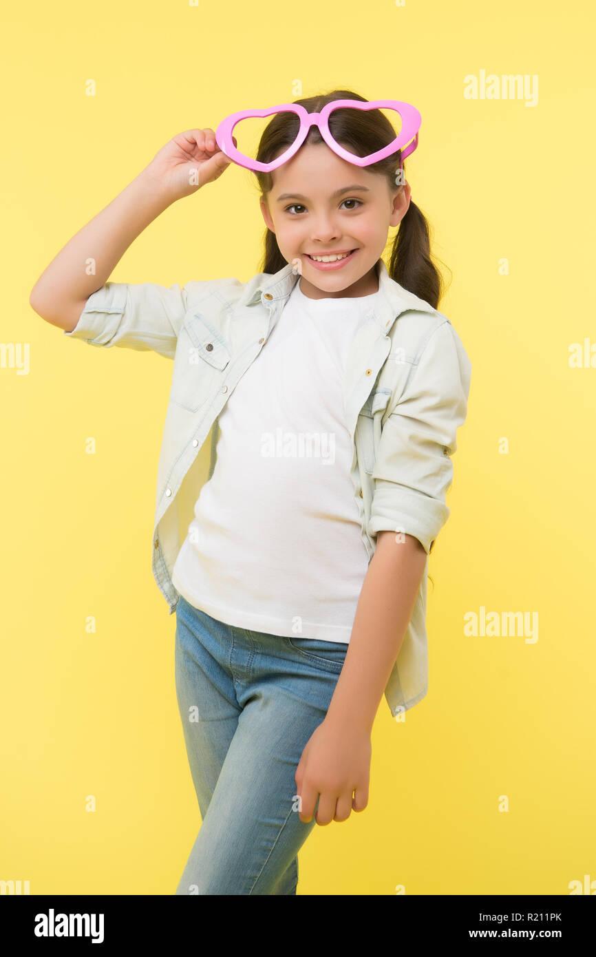 Ser mi Valentín. Niño encantadora sonrisa fondo amarillo. Niño feliz precioso siente simpatía. Chico Chica gafas en forma de corazón celebra el día de San Valentín. Chica adorable rostro sonriente corazón gafas. Imagen De Stock
