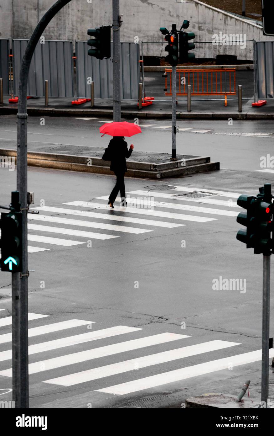 Mujer de caminar sobre el paso de peatones en la lluvia con la sombrilla roja Imagen De Stock