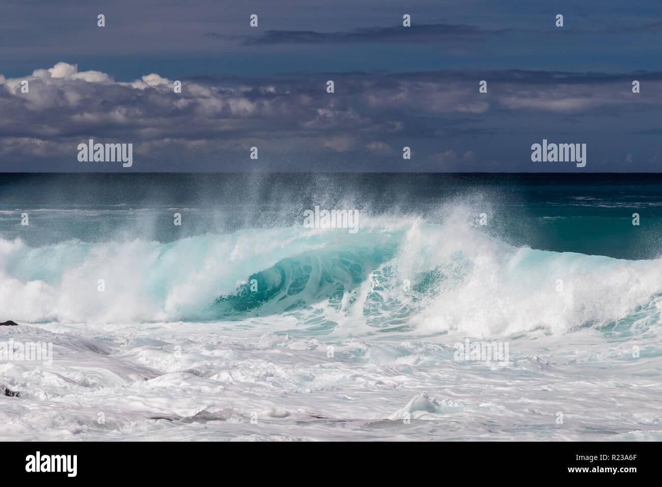 Ola curling en hawaiano Kona, cerca de la playa. Spray de volar de regreso en la parte superior de la onda. Espuma de oleada anterior en primer plano. Mar Blanco spray lanzados al aire. Foto de stock