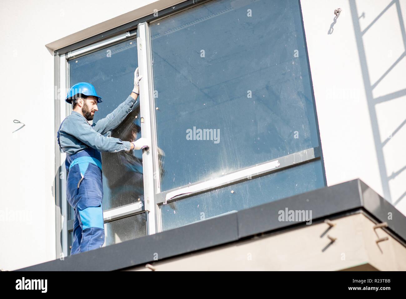 163bfd4bb8 Montaje uniforme obrero en windows control del plano vertical de pie en el  balcón del edificio