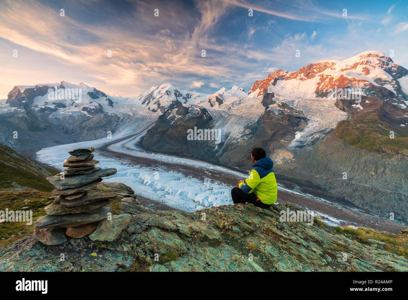 Caminante sentada sobre las rocas, mirando hacia el glaciar del Monte Rosa, Zermatt, cantón de Valais, Suiza Alpes, Suiza, Europa Imagen De Stock