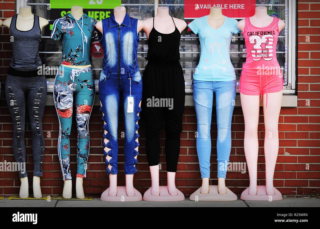 08f14eac3 Ropa para mujeres jóvenes sobre maniquíes muestran fuera de una tienda.