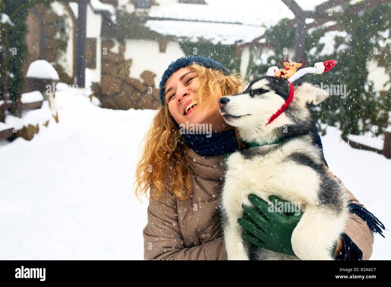 Atractiva mujer caucásica abrazos gracioso malamute perro vistiendo santa queridos astas de navidad. Rizado mujer sonriente divirtiéndose con cachorro huskie en año nuevo. El Pet es el mejor regalo. Doggy lamer cara de la niña. Foto de stock