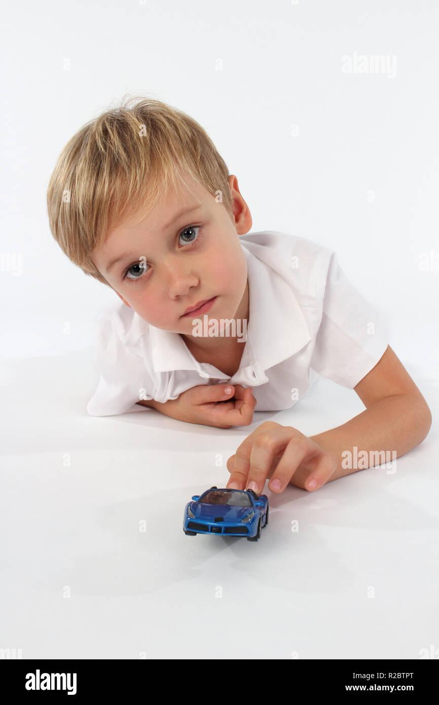 Lindo rubia de ojos azules pequeño niño jugar con juguetes de coche Imagen De Stock