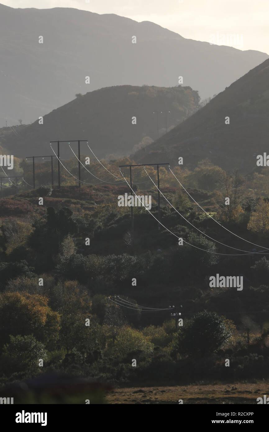 Las líneas eléctricas de alta tensión cruzan la ladera de la montaña, glencar, condado de Kerry, Irlanda Imagen De Stock