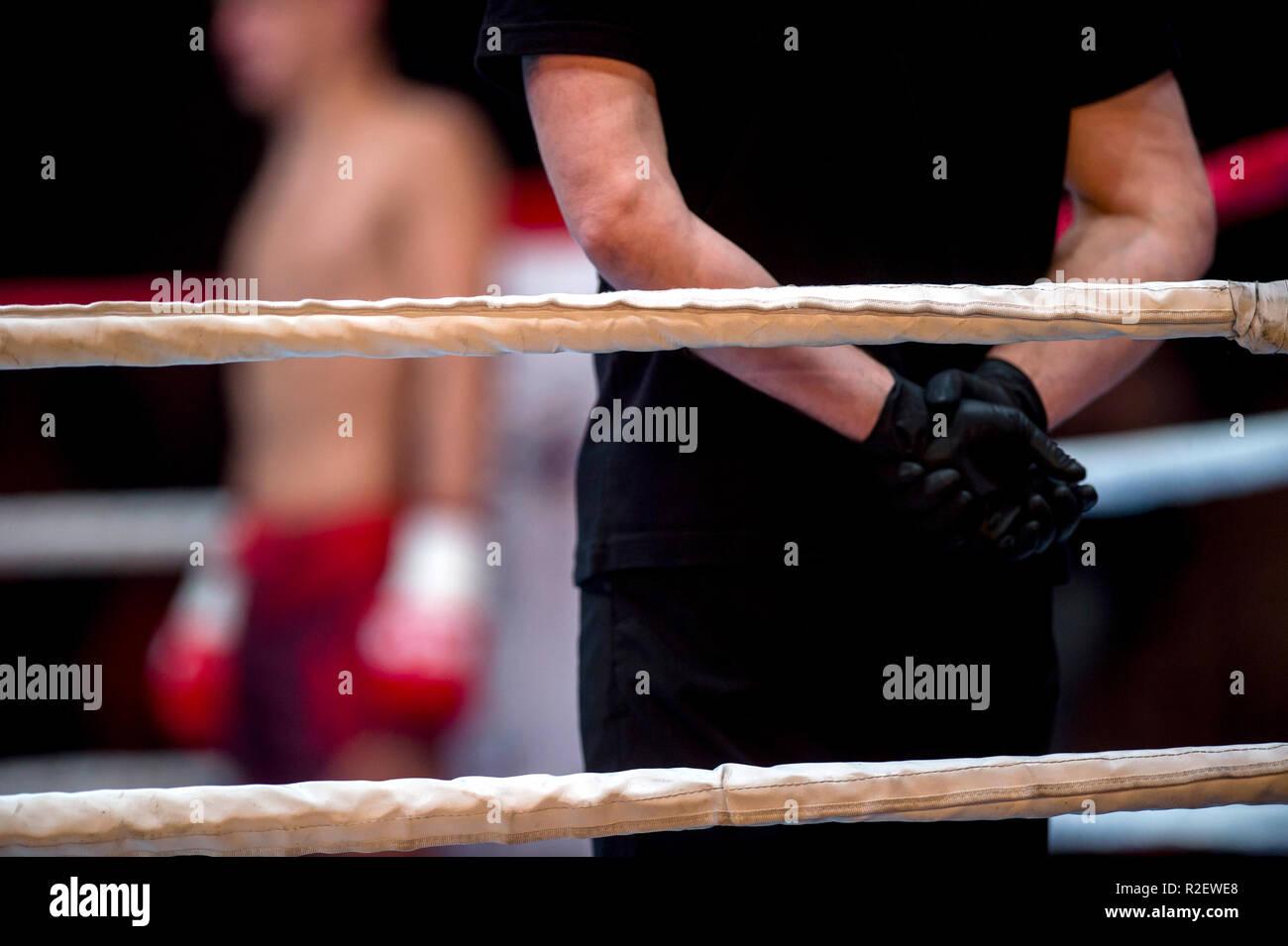 Cuadrilátero de boxeo cuerdas y árbitro en ropa negra en la corona dos luchadores MMA, competencia de Artes Marciales Boxeo Imagen De Stock