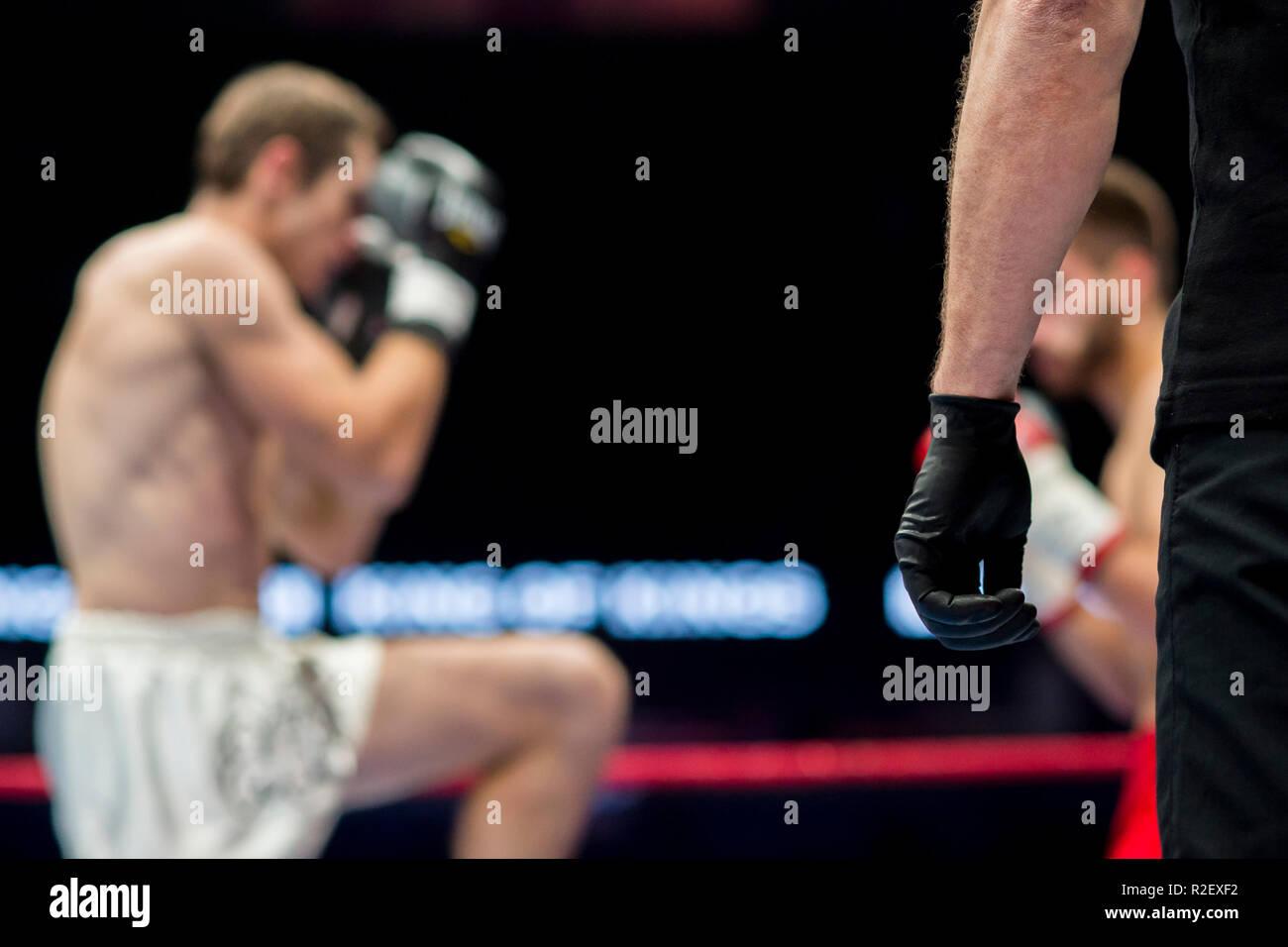 Árbitro en ropa negra en la corona dos luchadores MMA, competencia de Artes Marciales Boxeo Imagen De Stock